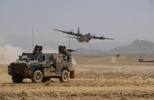 An Australian Bushmaster provides protection for an Australian C-130J that delivers stores and equipment to the Reconstruction Task Force troops in Southern Afghanistan.